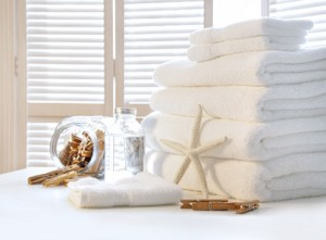 Fluffy white towels on table with shutter door